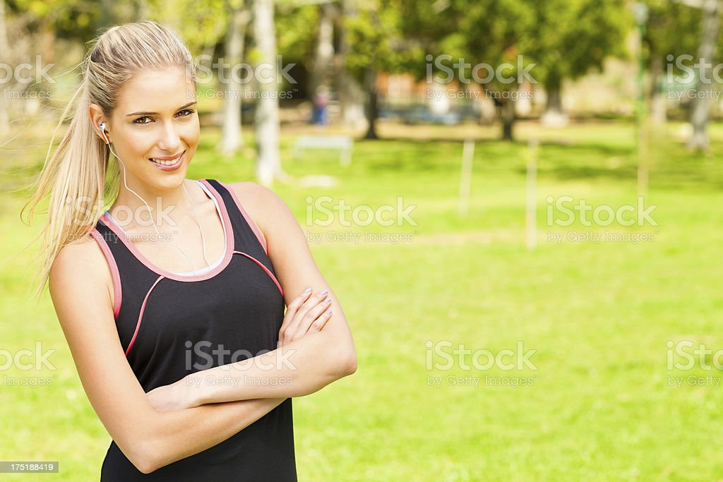 Young Woman With Arms Crossed Listening To Music At Park. royalty-free stock photo