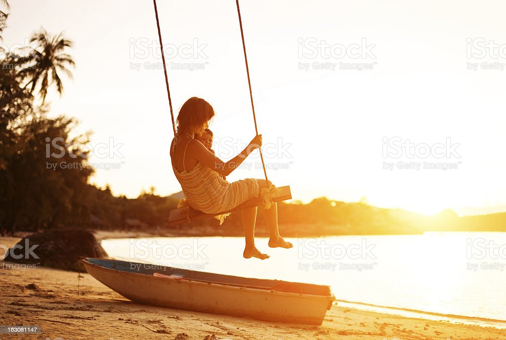 young woman with baby on beach swing stock photo