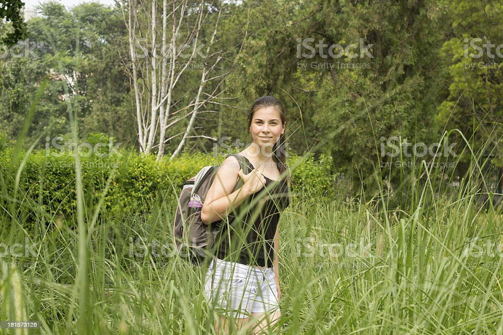 Young woman with backpack hiking at summer in forest royalty-free stock photo