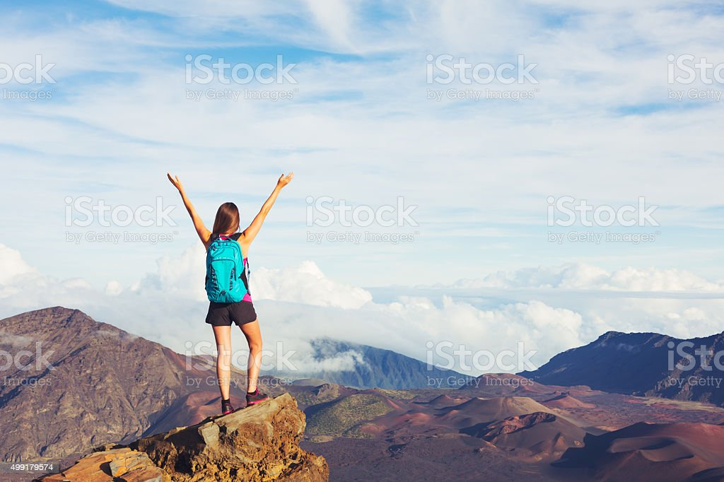 Young Woman with Backpack on Mountain Peak with Open Arms stock photo