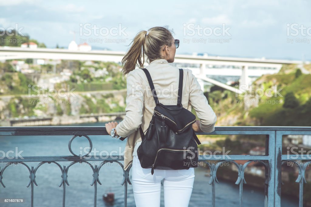Young woman with backpack walking on the european streets stock photo