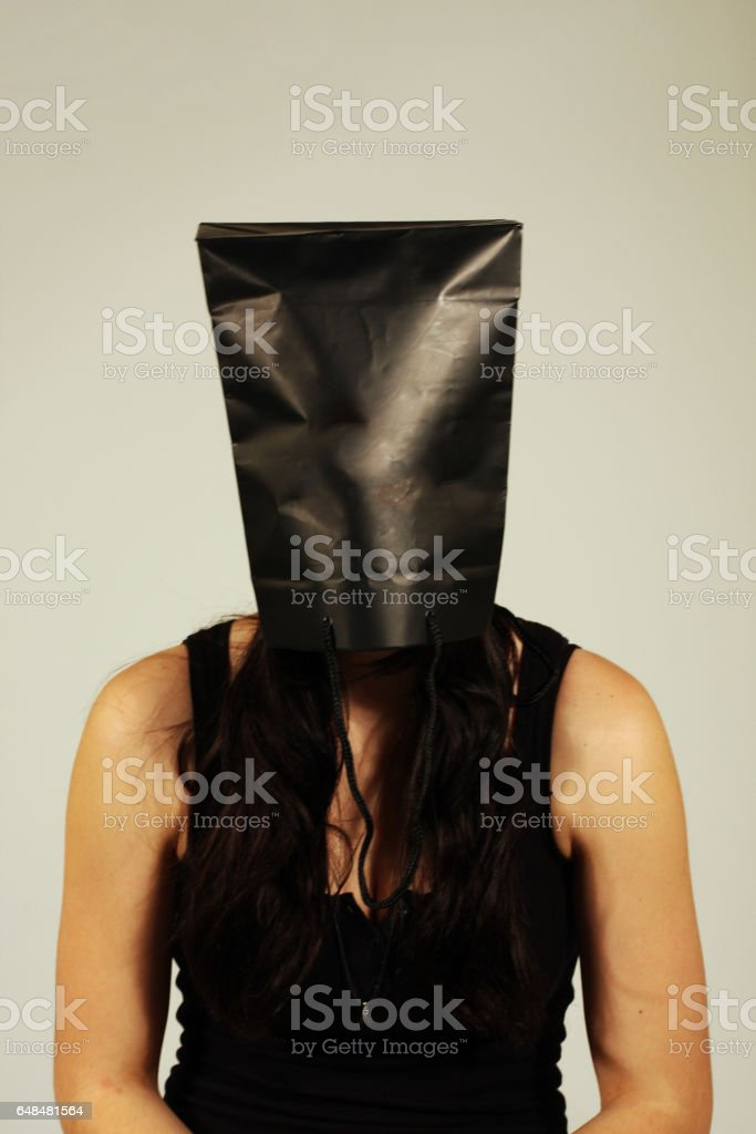 Young woman with bag over her head stock photo