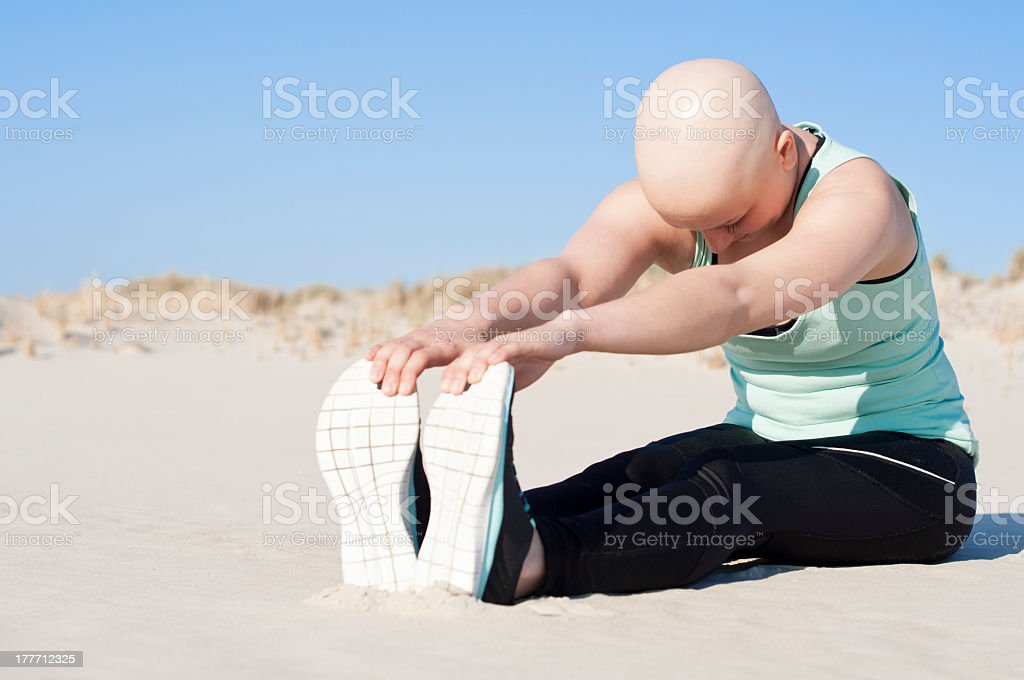 young woman with bald head stretching on beach after chemotherapy royalty-free stock photo