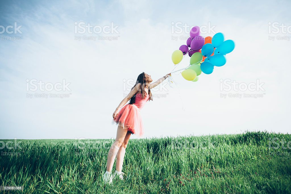 Young woman with balloons blown away by the wind stock photo
