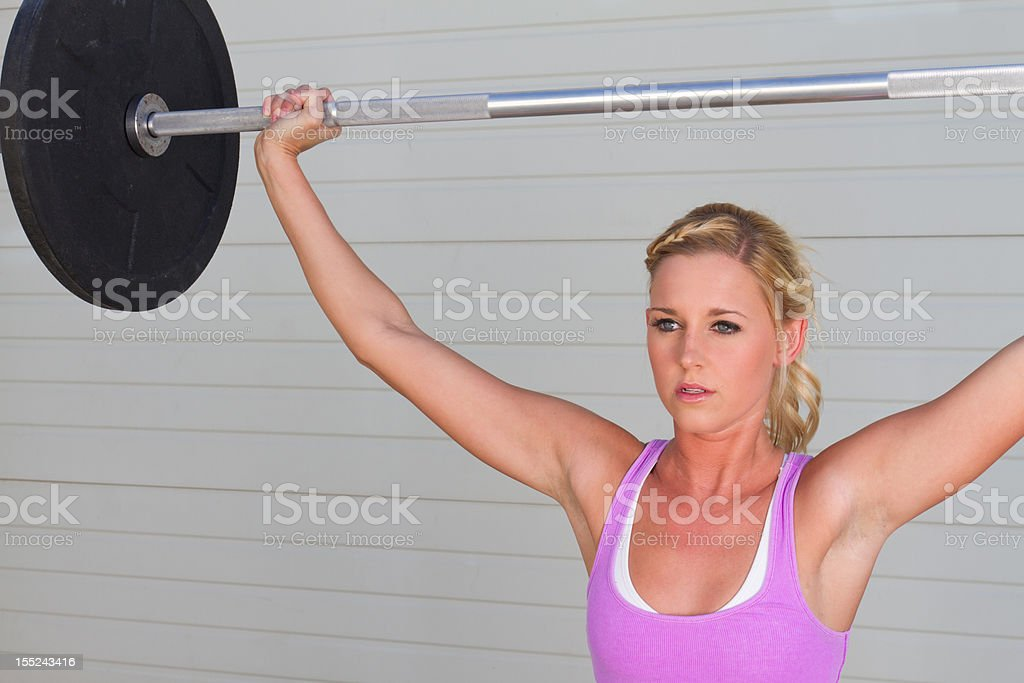 Young Woman with Barbell Overhead royalty-free stock photo