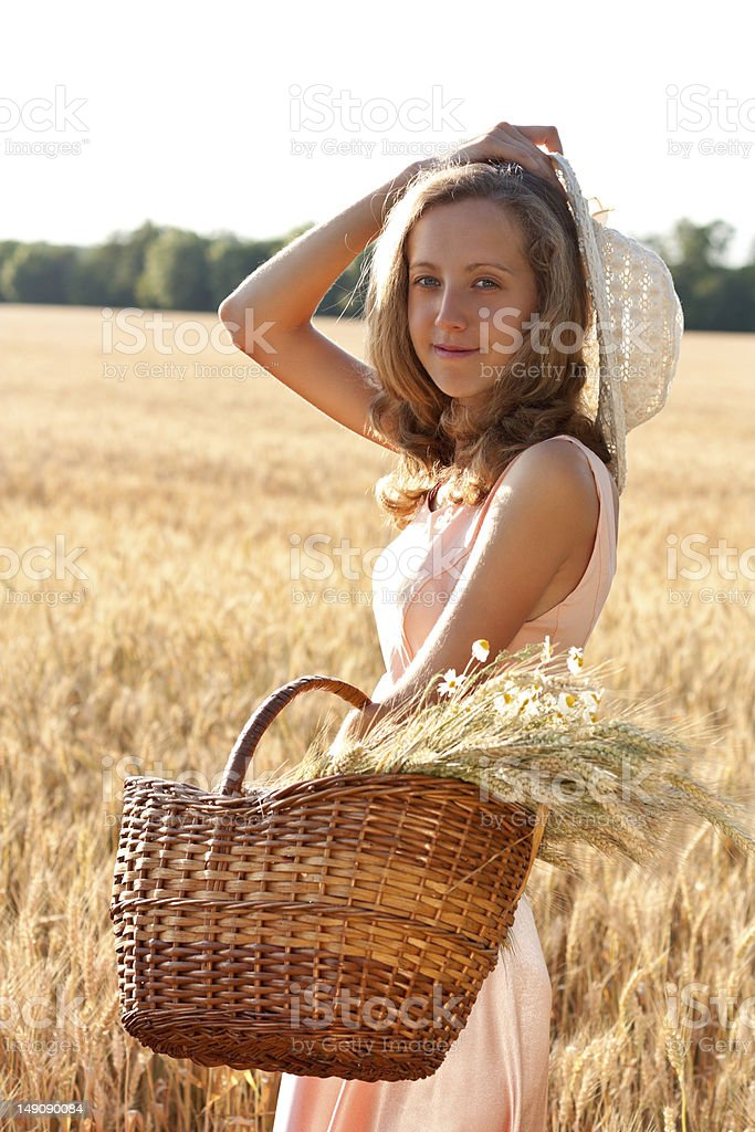 Young woman with basket full of ears wheat and hat royalty-free stock photo