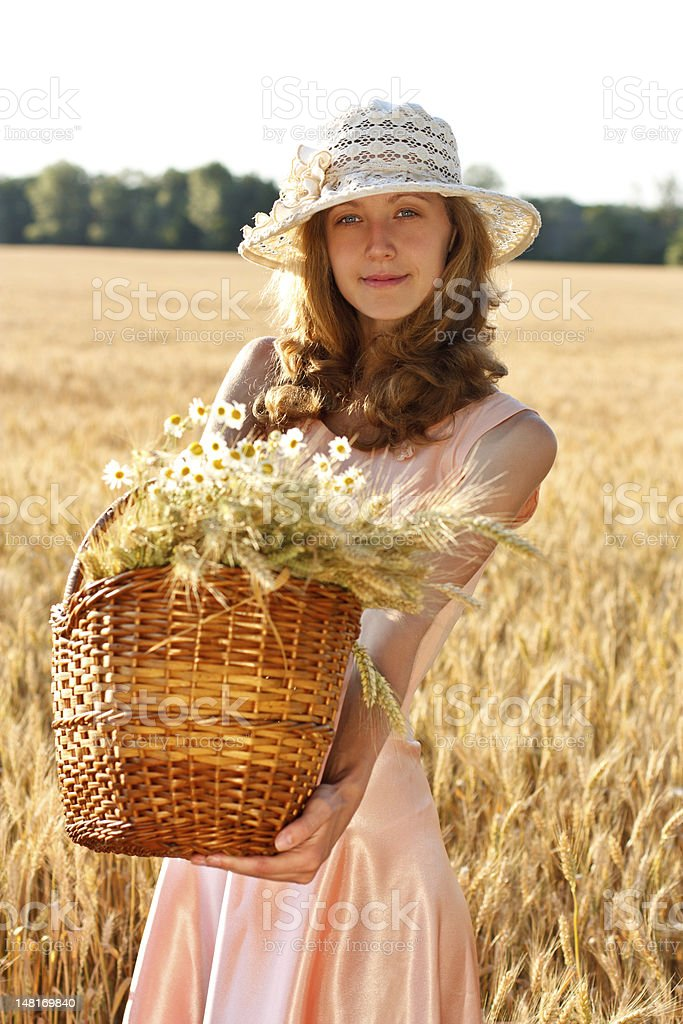 Young woman with basket full of ripe spikelets wheat royalty-free stock photo
