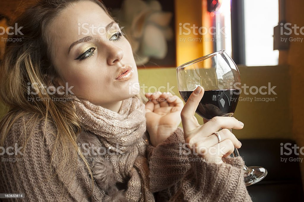 Young Woman with Beautiful Blue Eyes Drinking Red Wine stock photo