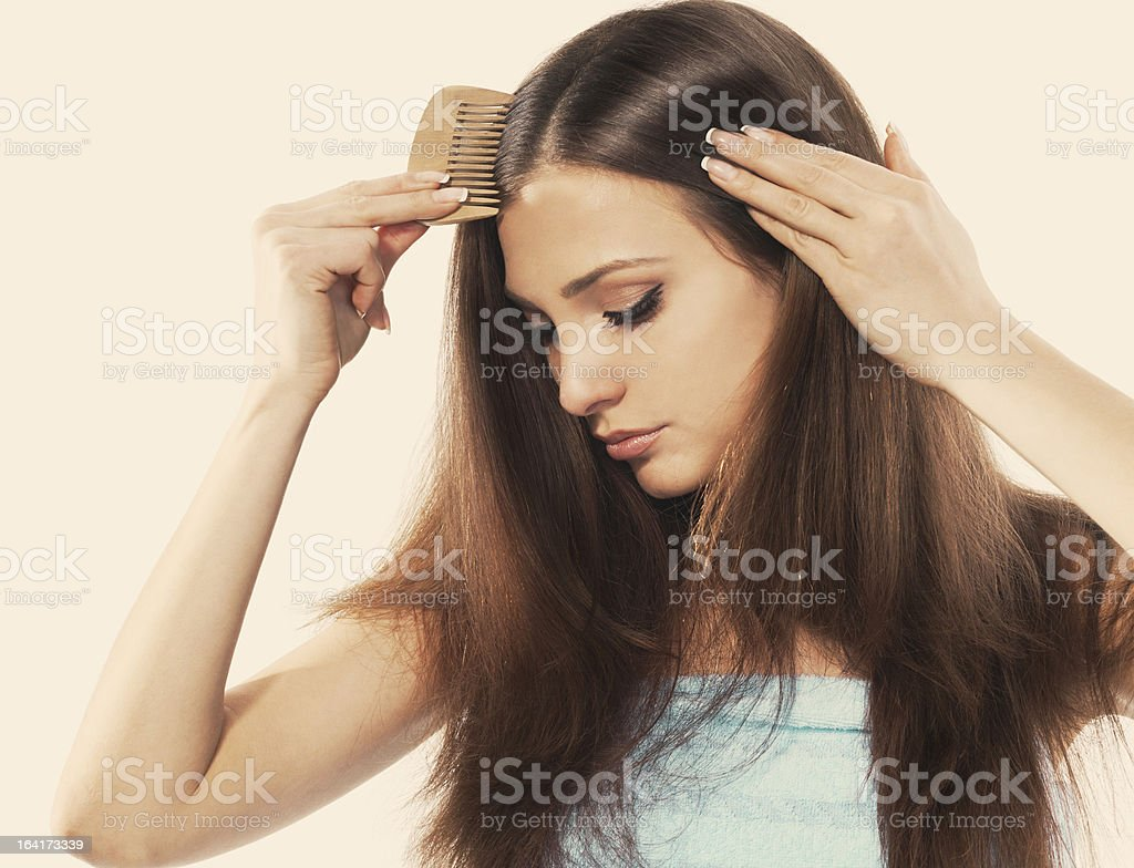 A young woman with beautiful long hair combing her locks stock photo