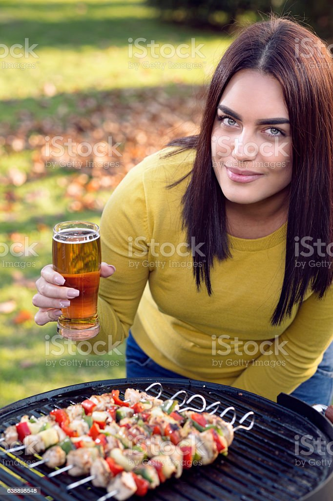 Young woman with beer and BBQ stock photo