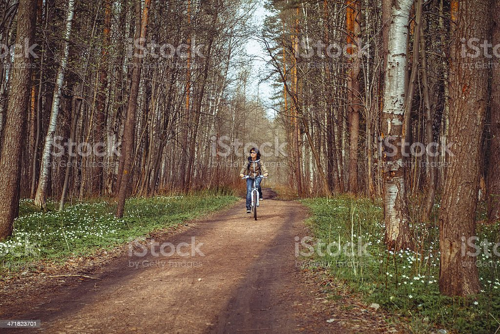 Young woman with bicycle on a road royalty-free stock photo