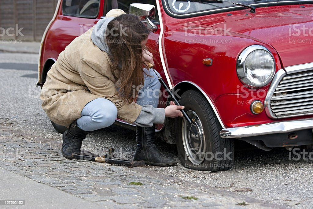 Young woman with bicycle pump and punctured tire royalty-free stock photo