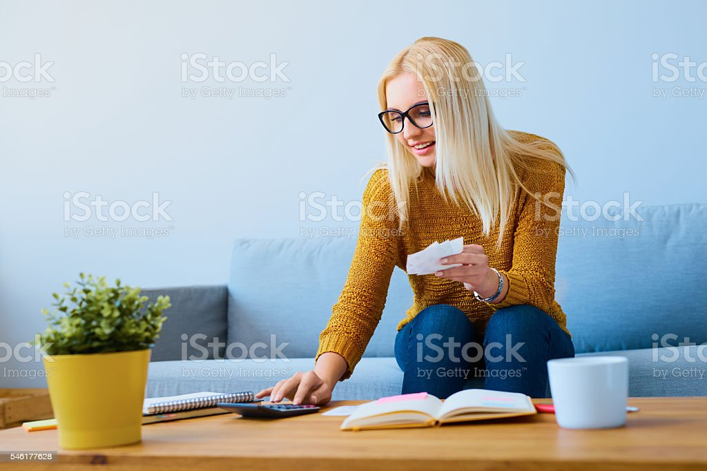 Young woman with bills calculating finances, sitting on sofa stock photo