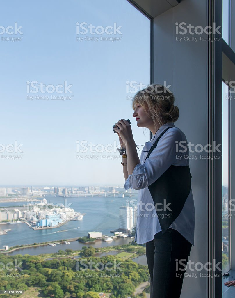 Young woman with binoculars in observation tower. stock photo