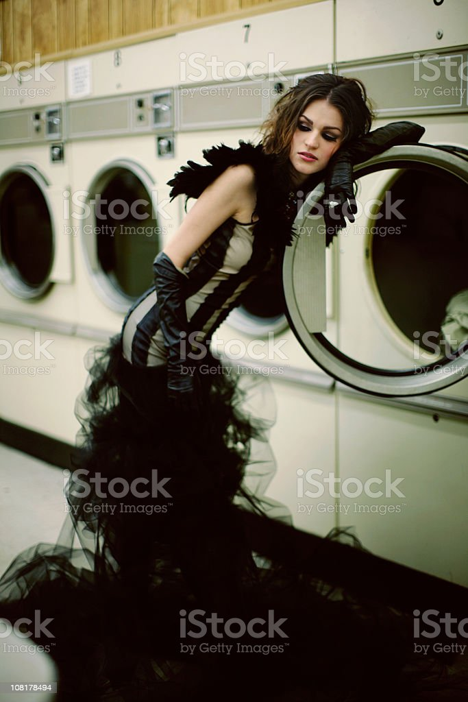 Young Woman with Black Evening Dress in a Laundry Mat royalty-free stock photo