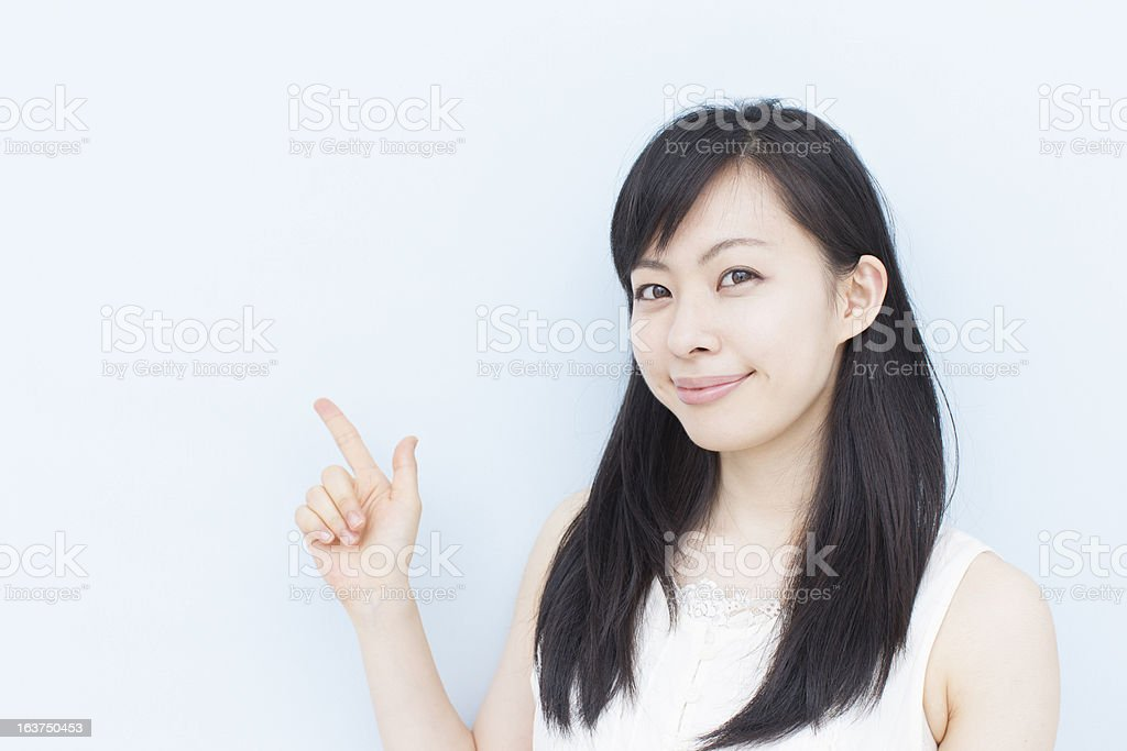 A young woman with black hair pointing upward royalty-free stock photo