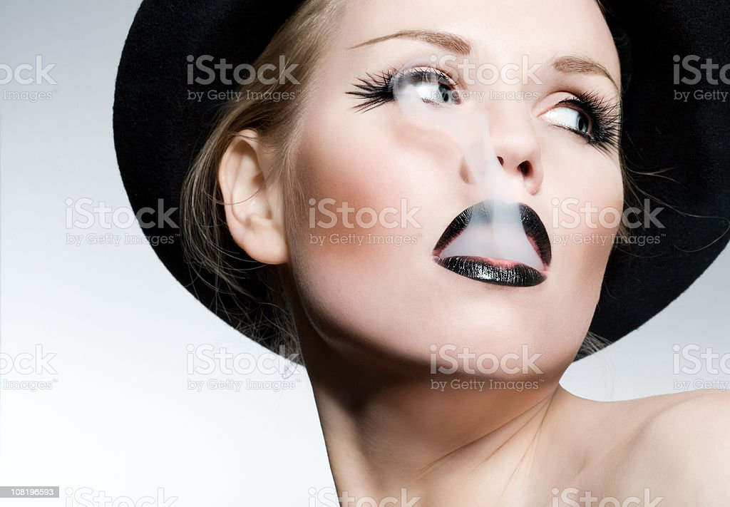 Young Woman with Black Lipstick Smoking stock photo