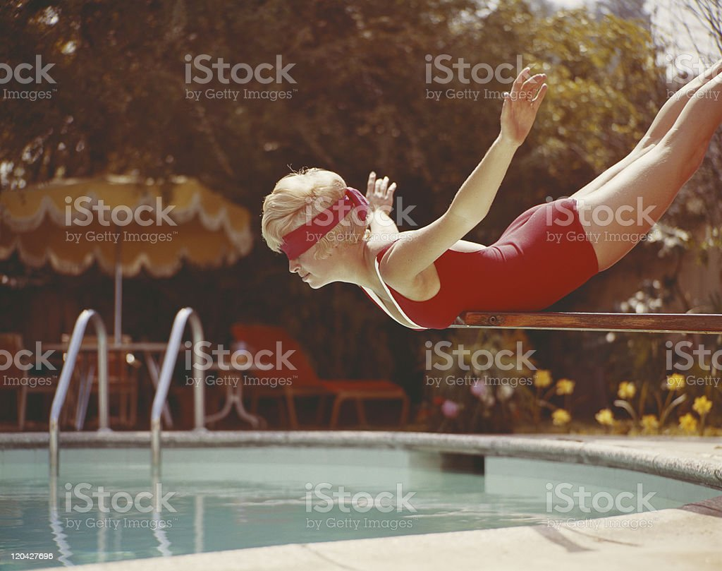 Young woman with blindfold balancing on diving board stock photo