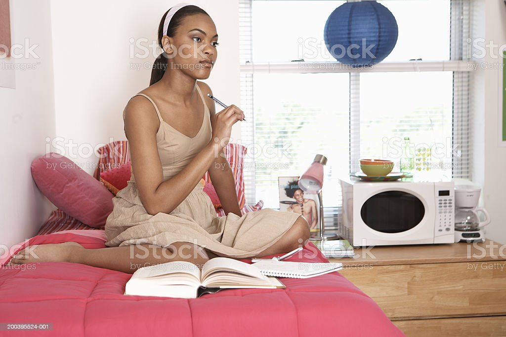 Young woman with books on bed in dorm room stock photo
