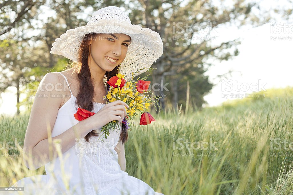 Young woman with bouquet of wildflowers sitting on grass outdoors royalty-free stock photo