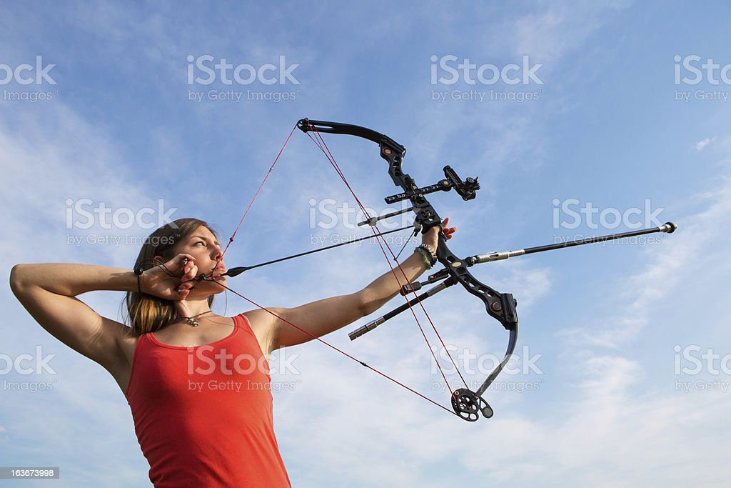 Young woman with bow and arrow practicing target shooting royalty-free stock photo
