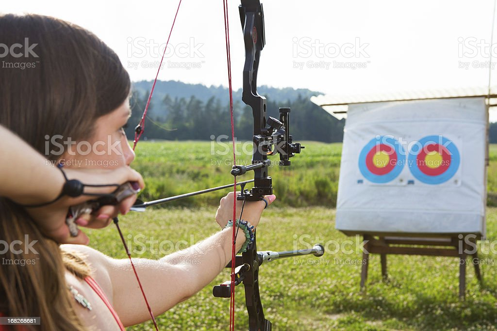 Young woman with bow and arrow practicing target shooting stock photo