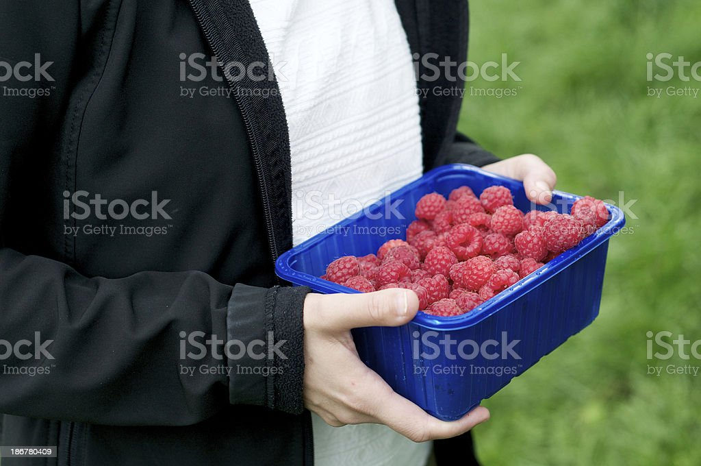 young woman with bowl of raspberries royalty-free stock photo