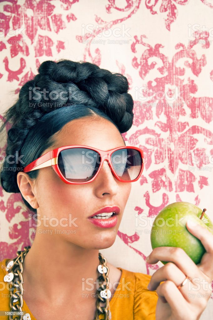 Young Woman With Braids on Head and Sunglasses Eating Apple royalty-free stock photo