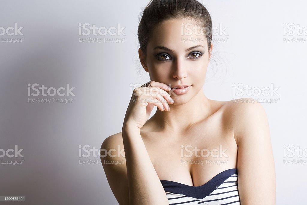 A young woman with brunette hair is standing  stock photo