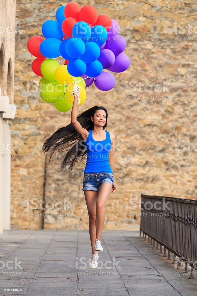 Young woman with bunch of balloons jumping on bridge stock photo
