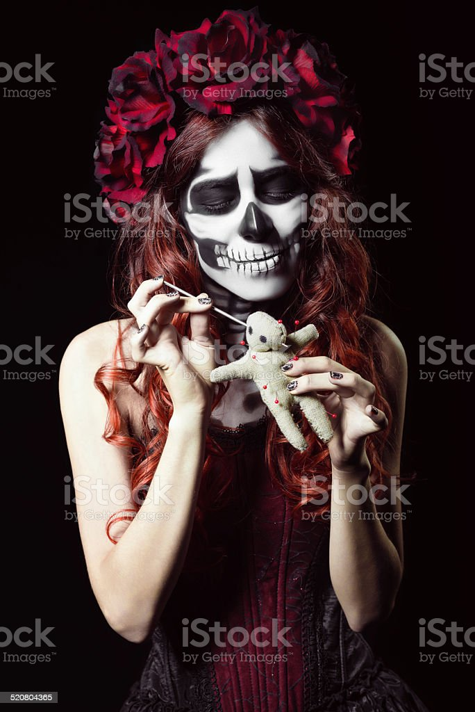 Young woman with calavera makeup (sugar skull) piercing voodoo doll stock photo