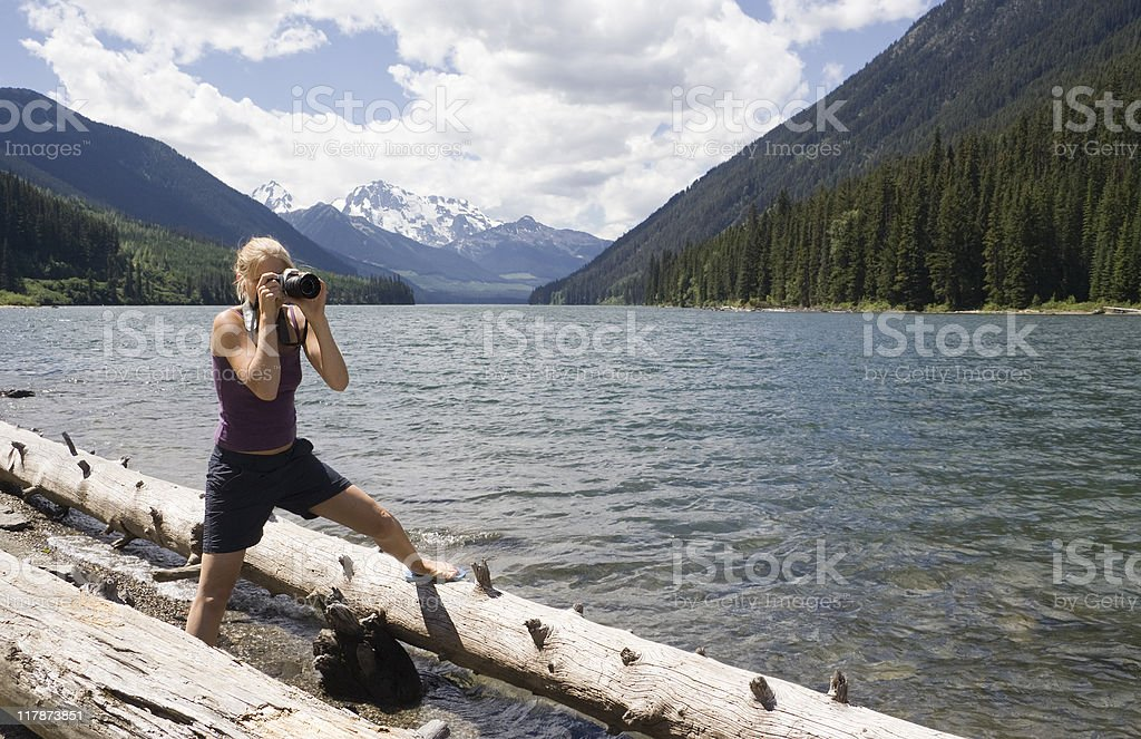 Young Woman with Camera on Floating Logs stock photo