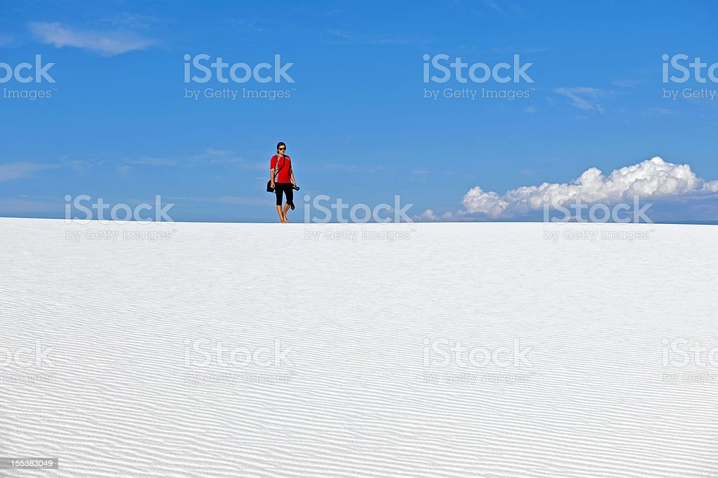 Young Woman with Camera Walking on Horizon White Sands USA stock photo