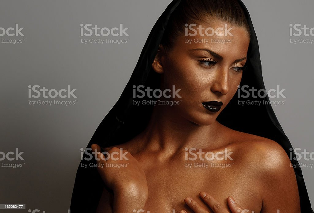 Young woman with cape and bronzed skin royalty-free stock photo