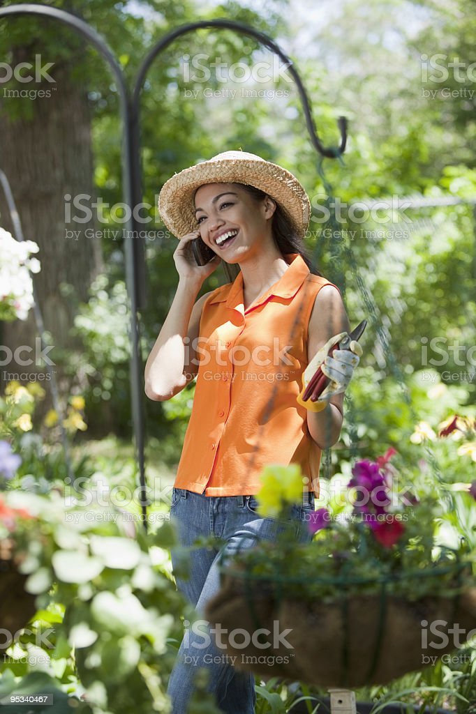 Young Woman With Cell Phone in Garden royalty-free stock photo