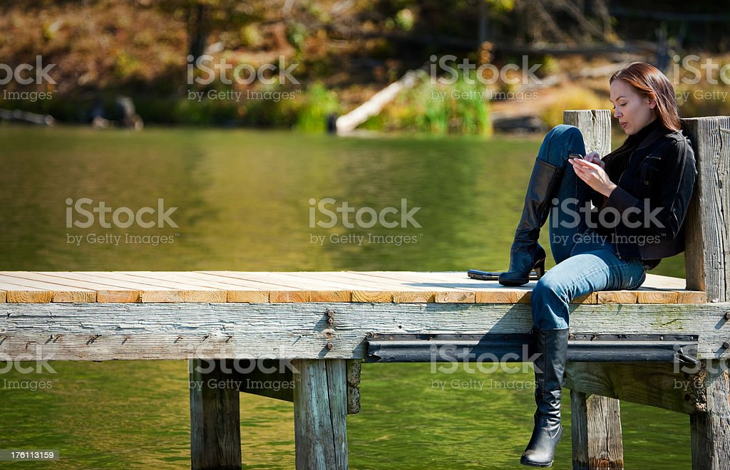 Young woman with cell phone on dock royalty-free stock photo