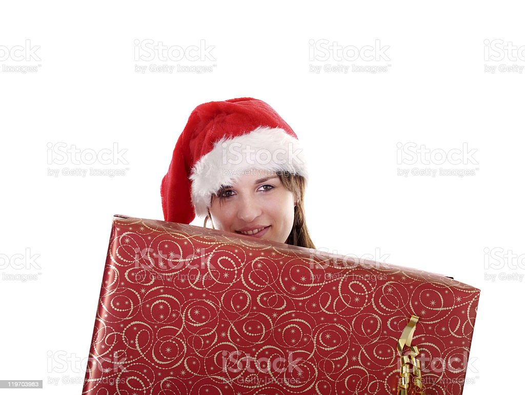 young woman with christmas hat behind a big present stock photo