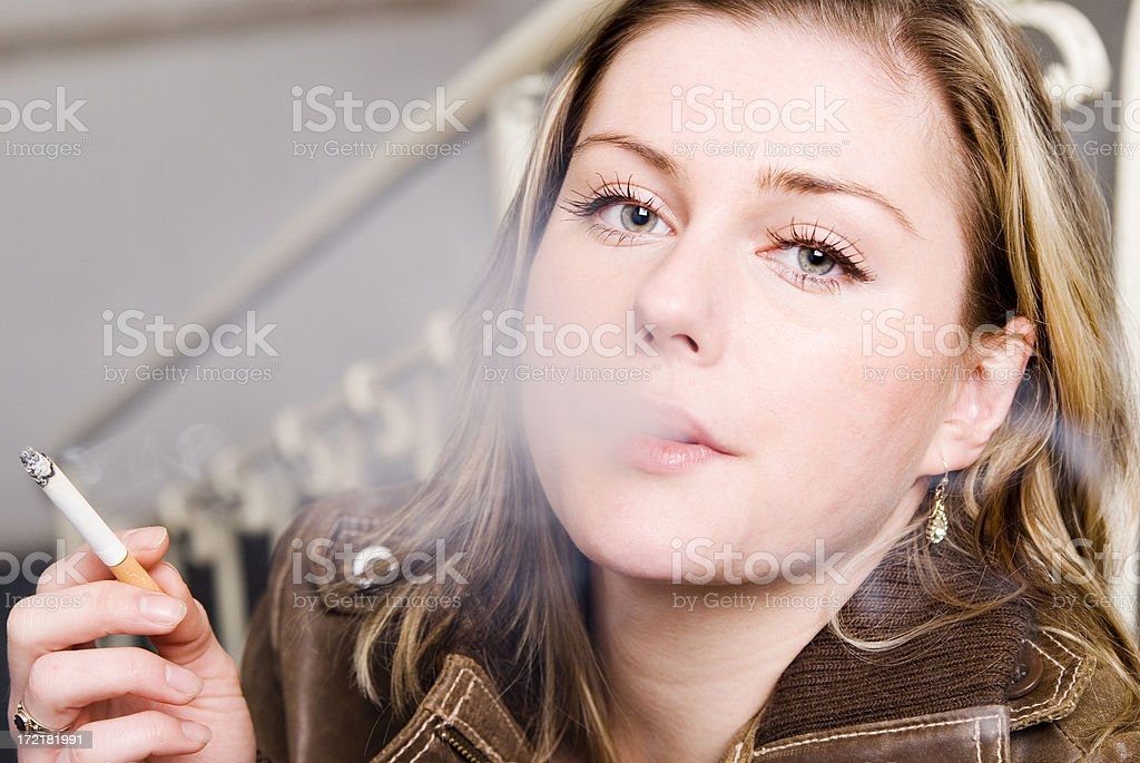Young Woman With Cigarette And Blowing Smoke royalty-free stock photo