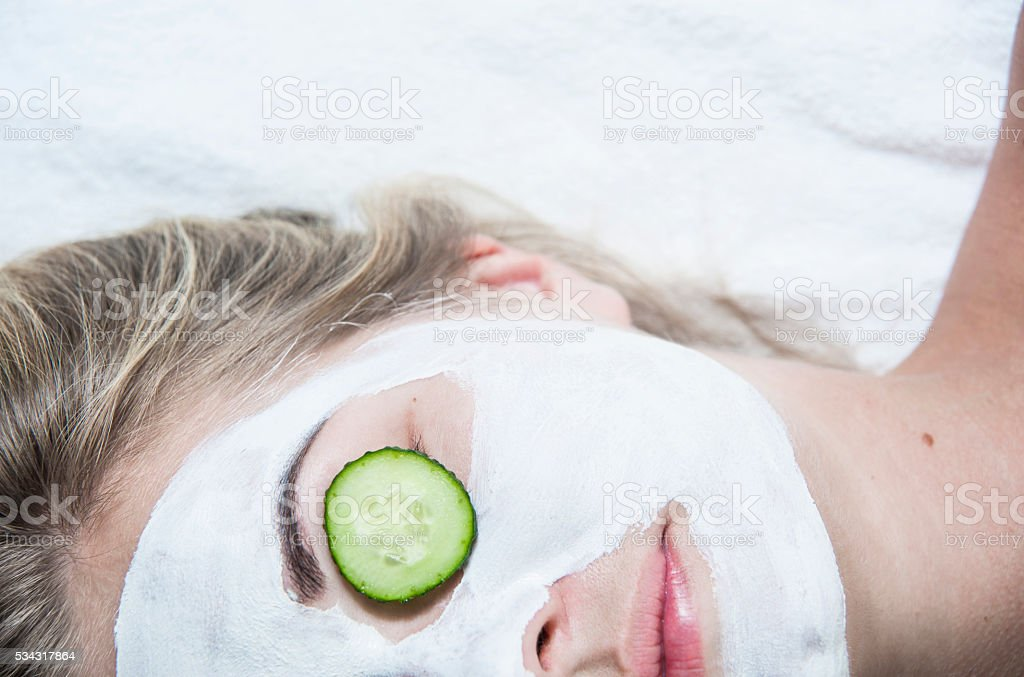 Young woman with clay facial mask in spa salon stock photo