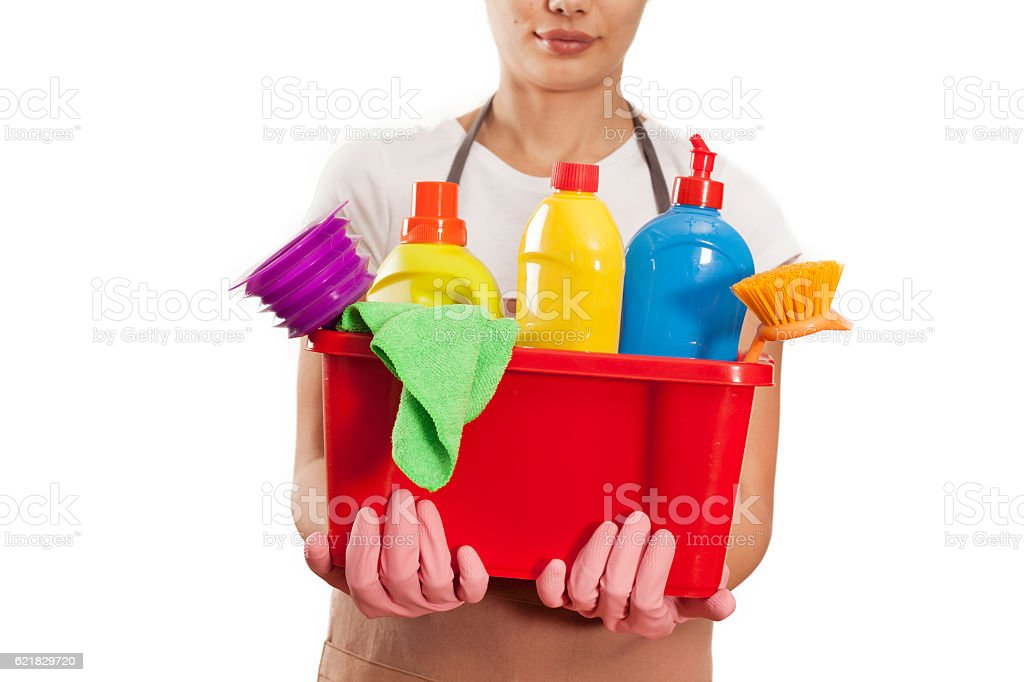 Young woman with cleaning supplies on white background stock photo