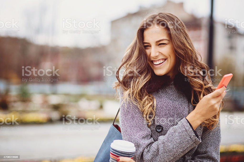 Young woman with coffee cup and phone smiling outdoors stock photo