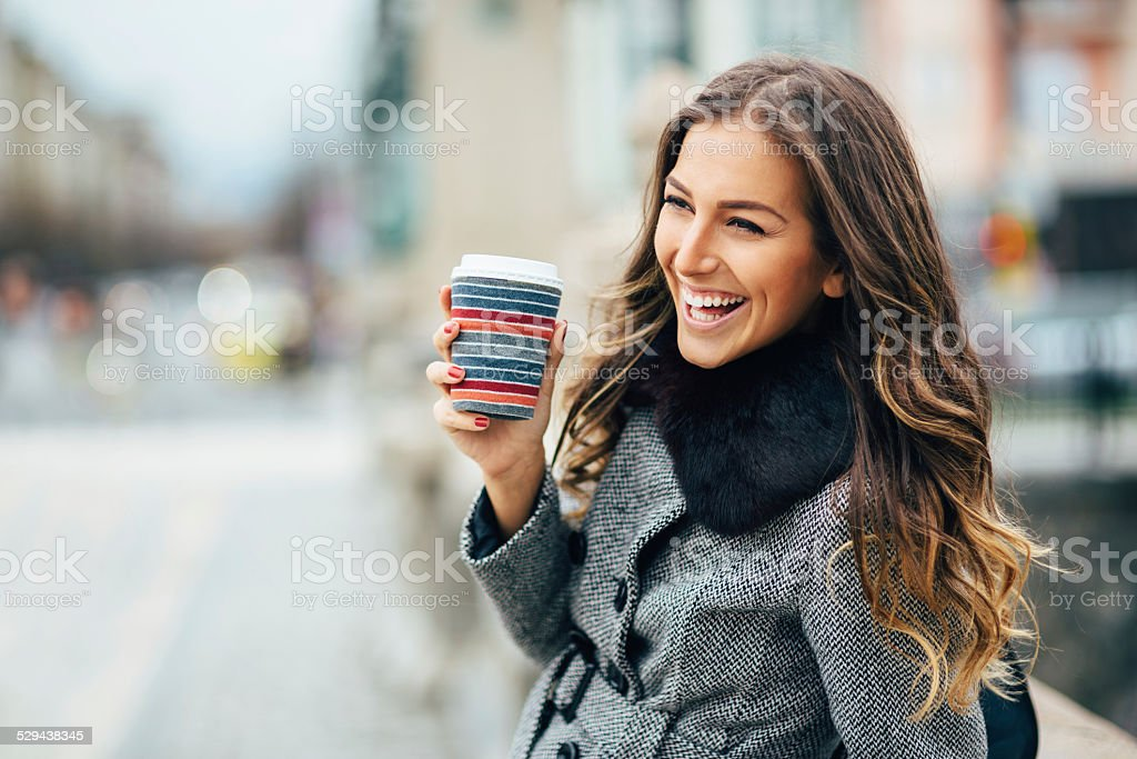 Young woman with coffee cup smiling outdoors stock photo