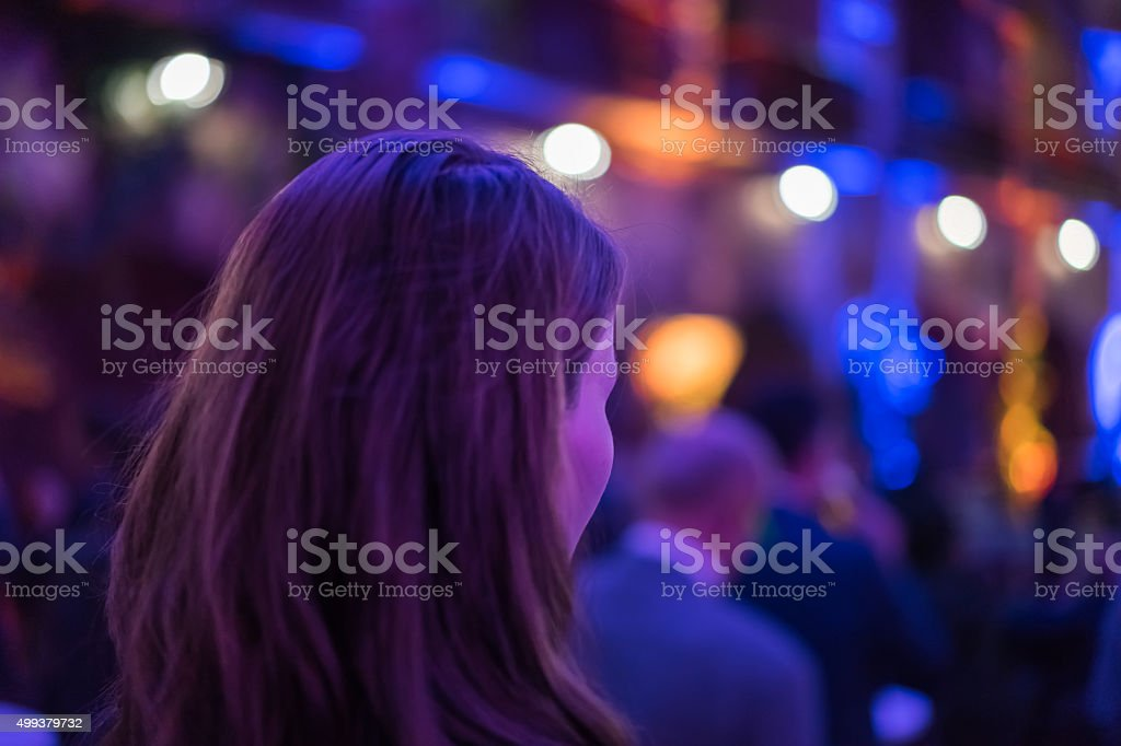 Young woman with colorful background lights stock photo