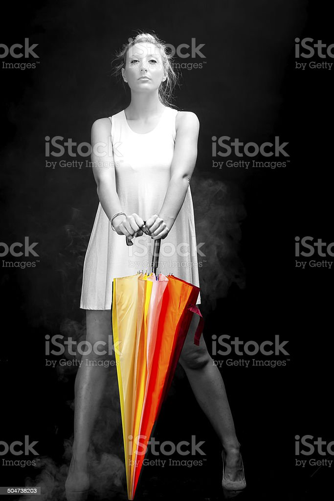 Young woman with colorful umbrella. Monochrome image stock photo