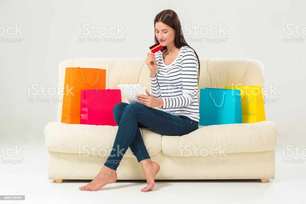 Young woman with credit card buying sitting on sofa with paper bags and new clothes stock photo