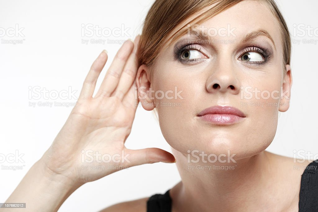 Young woman with cupping hand behind ear and eavesdropping stock photo