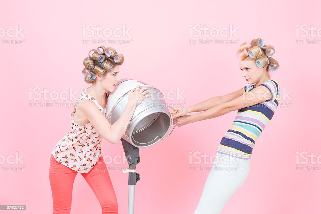 Young woman with curlers, quarreling about hood drier stock photo