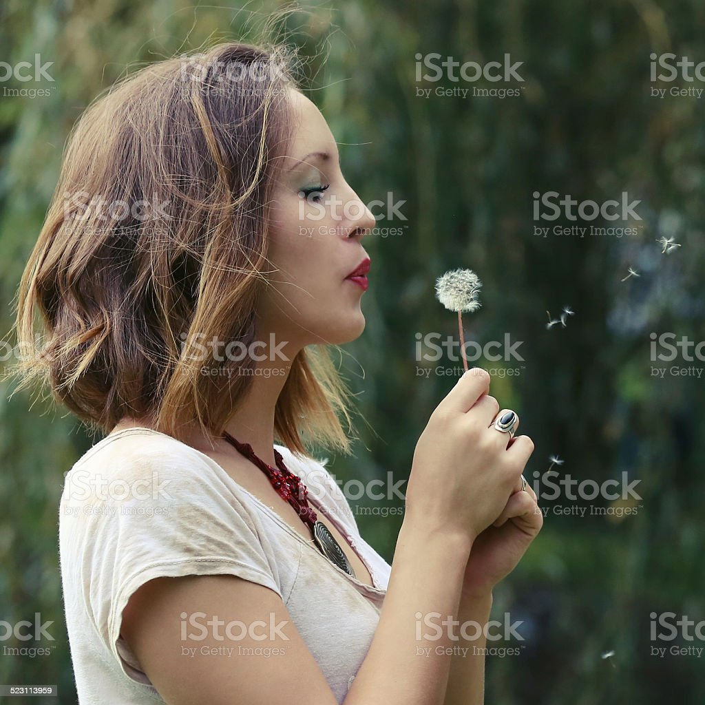 Young woman with dandelion stock photo