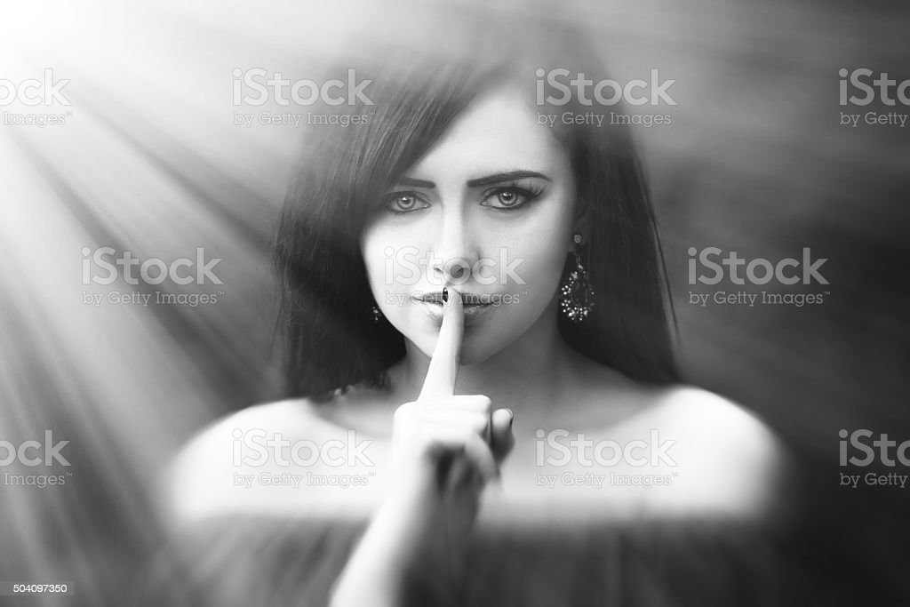 Young woman with dark long hair saying shh stock photo