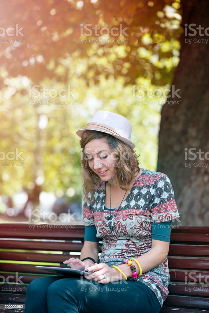 Young woman with digital tablet at the park stock photo